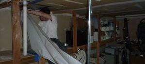 Water Damage Restoration Technician Removing Vapor Barrier
