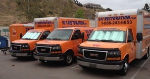 Water Damage Restoration and Mold Removal Vehicles At Commercial Job Site